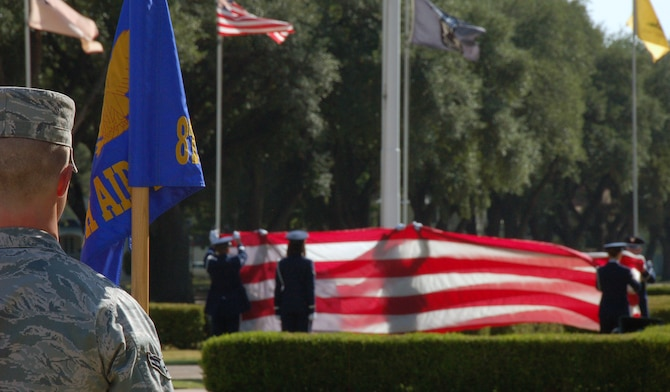 BARKSDALE AIR FORCE BASE, La. – Airman 1st Class Joshua Freedman, 608th Air and Space Operations Center, stands at attention as members of the 2nd Bomb Wing Base Honor Guard prepare to fold the U.S. flag during a retreat ceremony Aug.10, 2011, at Barksdale Air Force Base, La. The Eighth Air Force Headquarters and 2nd Medical Group performed the retreat ceremony, which serves a twofold purpose. It signals the end of the official duty day and serves as a ceremony for paying respect to the flag. When persons not assigned to a formation are outdoors and in uniform, on the first note of retreat, they should face the flag (if visible) or music and assume the position of parade rest. (U.S. Air Force photo by Staff Sgt. Brian Stives)