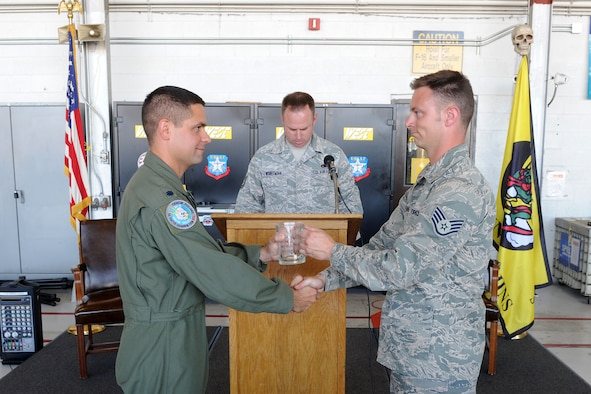 U.S. Air Force Lt. Col. Jay Sabia, left, 4th Fighter Squadron commander, and Staff Sgt. Brandon Fenner exchange presentations during a ceremony recognizing their assignments to specific aircraft in the 4th FS Aug. 5. These individuals were awarded the honor of dedicated crew chief for demonstrating superior performance in compliance with safety practices and technical requirements while displaying managerial skills and leadership abilities. (U.S. Air Force photo by Alex Lloyd)