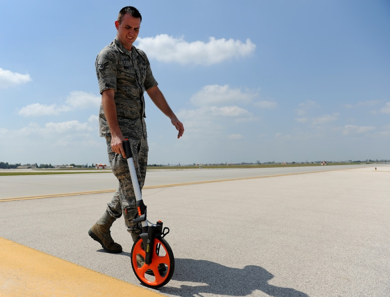 Airman 1st Class Phillip Rinde, 39th Operations Squadron airfield management apprentice, measures the width of a taxiway using a measuring-wheel gauge Aug. 10, 2011, at Incirlik Air Base, Turkey. Airfield management measures the taxiways to make sure they are wide enough for aircraft and to ensure lines are the correct size and distance from each other. (U.S. Air Force photo by Senior Airman Anthony Sanchelli/Released)