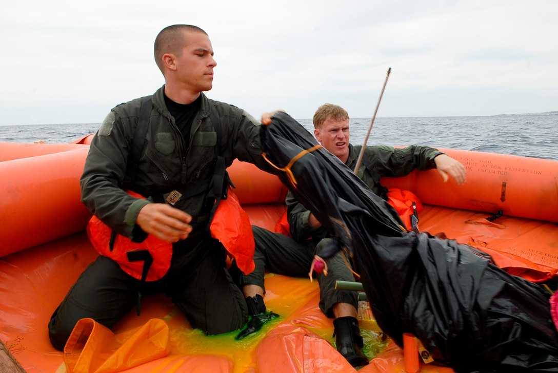 Capt. Chris Moran, 909th Air Refueling Squadron KC-135 pilot, and 1st Lt. Ross Hapkin, 909th Air Refueling Squadron KC-135 copilot, tear down a canopy they helped construct on a life raft during a water survival refresher course Aug. 11 at the Kadena Marina in Okinawa, Japan. Radio use, survival techniques and health risks were topics aircrew members reviewed while taking the refresher course. (U.S. Air Force photo/ Airman 1st Class Tara A. Williamson)