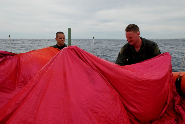 Capts. Chris Moran and Travis Epp, 909th Air Refueling Squadron KC-135 pilots, find the edges of a tarp from a survival kit to make a canopy over a life raft during a water survival refresher course Aug. 11 at the Kadena Marina in Okinawa, Japan. This survival course is required every three years for aircrew members to familiarize themselves with the equipment and skills needed if they find themselves making a water landing. (U.S. Air Force photo/ Airman 1st Class Tara A. Williamson)