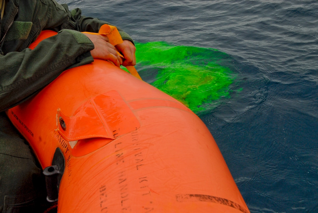 Senior Airman Dan Childress, 909th Air Refueling Squadron KC-135 boom operator, submerges a package of sea dye while in a life raft during a water survival refresher course Aug. 11 at the Kadena Marina in Okinawa, Japan. Sea dye, radios, survival techniques and health risks were topics aircrew members reviewed while taking the refresher course. (U.S. Air Force photo/ Airman 1st Class Tara A. Williamson)