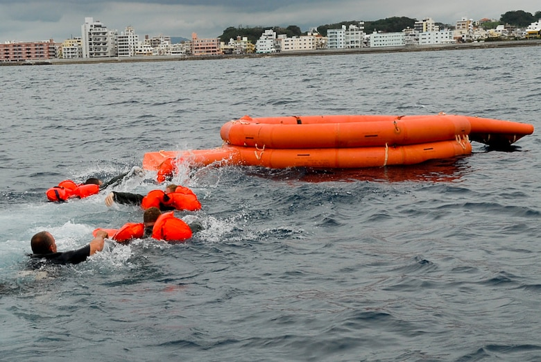 Four aircrew members and Staff Sgt. William Lambert, 18th Operations Group Survival, Evasion, Resistance, and Escape specialist, swim to a life raft during a water survival refresher course Aug. 11 at the Kadena Marina in Okinawa, Japan. This survival course is required every three years for aircrew members to familiarize themselves with the equipment and skills needed if they find themselves making a water landing. (U.S. Air Force photo/ Airman 1st Class Tara A. Williamson)