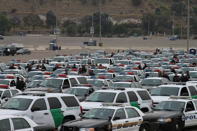 Hundreds of law enforcement vehicles, fire trucks and ambulances from several different police departments were parked in the Qualcomm Stadium parking lot Aug. 12. The vehicles were part of a funeral procession for Police Officer Jeremy Henwood that led to memorial services at the Rock Church.