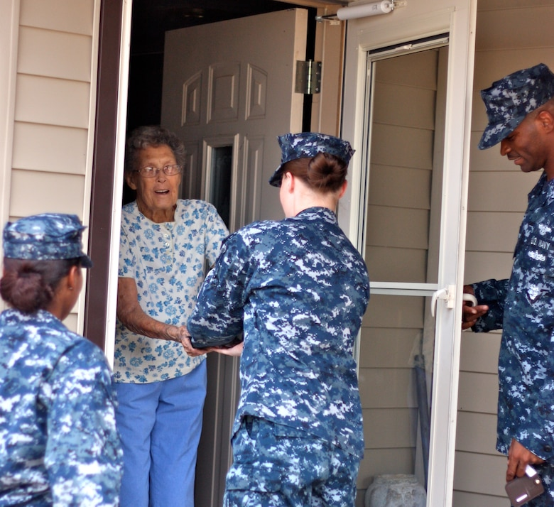 SAN ANGELO, Texas -- Merlie Smith, one of the Meals for the Elderly participants, receives her food from volunteer Navy Petty Officer 3rd Class Stephanie Hauge Aug. 12. (Courtesy photo/Whitney Haskell)