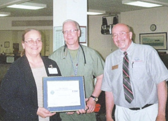 Staff Sgt. Thomas Garvey, center, a nurse at the Twin Ports Veterans Outpatient clinic, nominates his boss, Mary Kolosky, left, for the Employer Support of the Guard and Reserve Patriotic Employer award, presented by Terry Erickson, an ESGR volunteer, right. (Submitted photo)