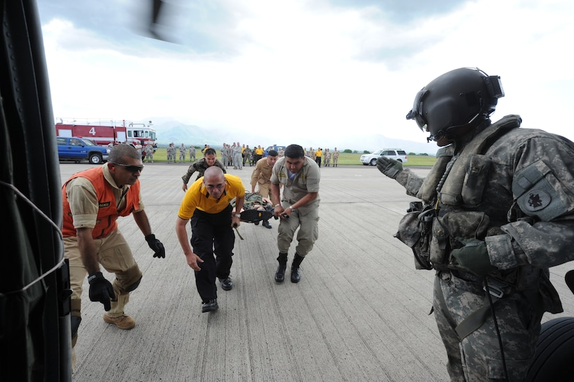 Honduran and Costa Rican firefighters bring a litter to a waiting UH-60 helicopter during an exercise at Soto Cano Air Base, Honduras, Aug. 16, 2011. The exercise, called Central America Sharing Mutual Operational Knowledge and Experiences or CENTAM SMOKE, allows U.S., Honduran and Costa Rican firefighters four days of team-building training. (U.S. Air Force photo/Tech. Sgt. Matthew McGovern)