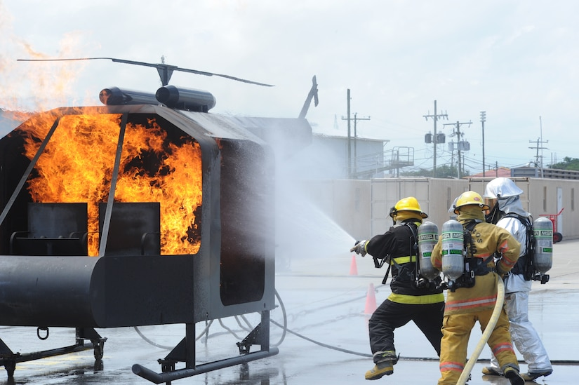 Mr. Renau Andrade (left) and Mr. Mauricio Alvarez, Costa Rican firefighters, extinguish a fire in a mock helicopter with pointers from Staff Sgt. Steven Beene, 612th Air Base Squadron firefighter, during an exercise at Soto Cano Air Base, Honduras, Aug. 16, 2011. The exercise, called Central America Sharing Mutual Operational Knowledge and Experiences or CENTAM SMOKE, allows U.S. and Honduran firefighters four days of team-building training. (U.S. Air Force photo/Tech. Sgt. Matthew McGovern)