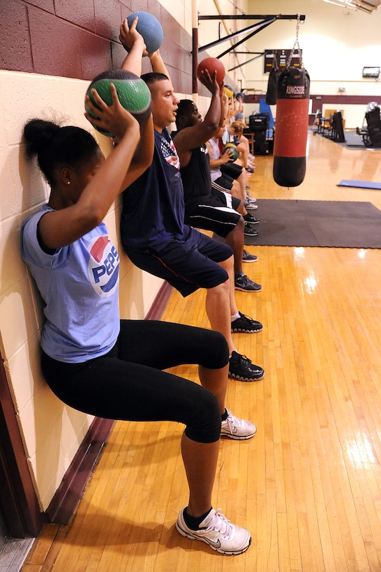 SEYMOUR JOHNSON AIR FORCE BASE, N.C.- Boot camp participants perform a wall squat with a medicine ball here Aug. 15, 2011. The wall squat is a leg isometric exercise that builds endurance and strength. Boot camp is available at the fitness center to all U.S. Air Force members, dependents and Department of Defense civilians. (U.S. Air Force photo by Senior Airman Whitney Lambert/Released)