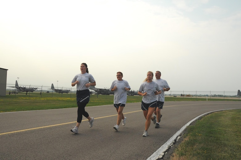 MSgt Melissa Shenefiel, MSgt Laura Thomas, TSgt Rachel Baker and MSgt Michael Margarucci doing their final phase of the PT test the 1 1/2 mile run.(Air Force Photo/SMSgt Ray Lloyd)