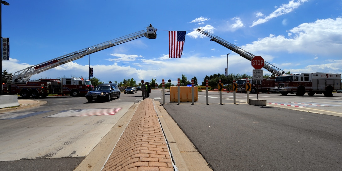 BUCKLEY AIR FORCE BASE, Colo. --  Chief Warrant Officer 4 David Carter's remains pass under a raised American flag Aug. 17, 2011. Carter perished in a helicopter crash in Wardak province, Afghanistan, Aug. 6, 2011. In support of the Colorado Army National Guard here at Buckley AFB, members of Team Buckley lined the streets to pay their final respect to a fallen brother. (U.S. Air Force photo by Senior Airman Marcy Glass)