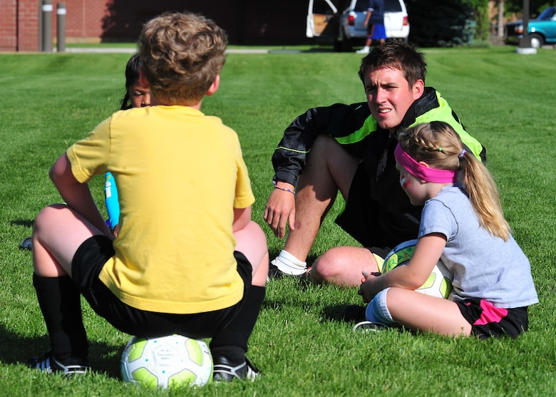 O'Brien takes a moment to get to know the kids before they start their soccer session Aug. 10. (U.S. Air Force photos/Staff Sgt. Michael Means)