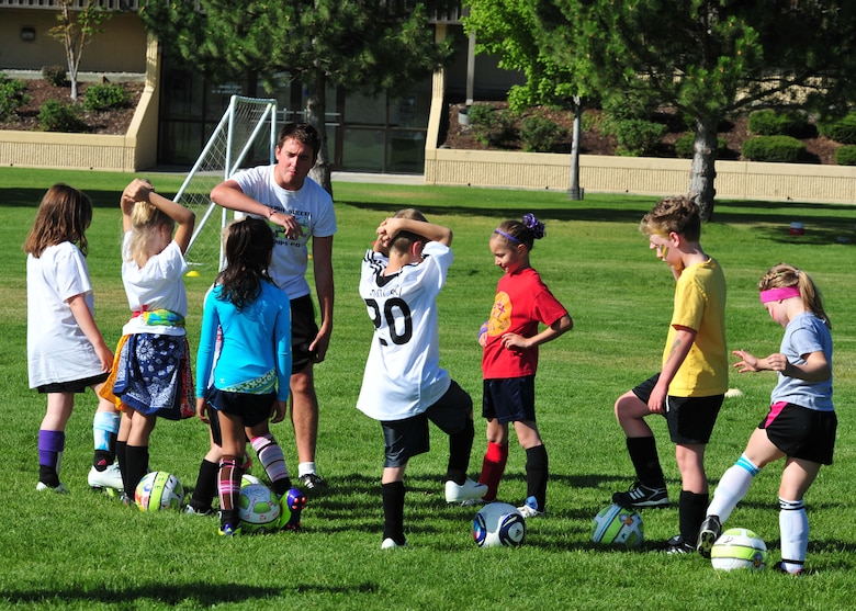 Anthony O'Brien, British soccer coach, runs practice drills with Fairchild youth Aug. 10. The Fairchild Youth Center partners with U.K.-based Challenger Sports to bring the British coaches to the base in an effort to broaden thier soccer and worldly knowledge. (U.S. Air Force photos/Staff Sgt. Michael Means)