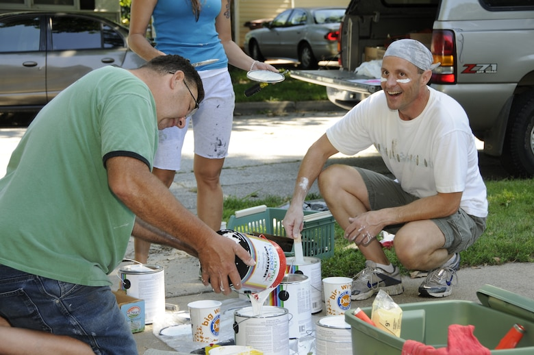 Chief Master Sgt. Douglas E. Schulz and Senior Master Sgt. Stuart P. Stofferahn pour and stir the paint used during the Lincoln Paint-a-thon in Lincoln, Neb. on Aug. 13, 2011. Schulz and Stofferahn coordinated the event and recruited volunteers.  (Nebraska Air National Guard photo by Master Sergeant Vern Moore) (Released)