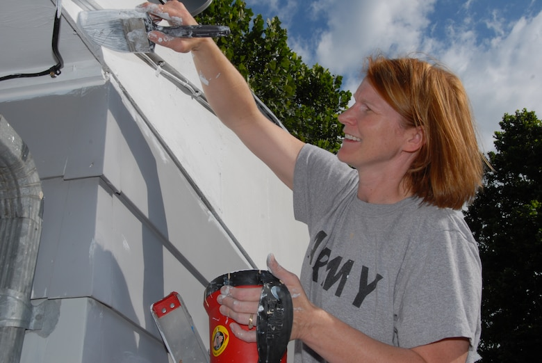 Army Sgt. 1st Class Pam Whisenhunt stood on a ladder as she painted the trim of the house during the National Paint-a-thon in Lincoln, Neb. on Aug. 13, 2011. Whisenhunt found out about the event through the Enlisted Association.  (Nebraska Air National Guard photo by Airman First Class Mary Thach) (Released)
