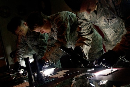 Staff Sgt. Michael Zimmerman, Tech. Sgt. Shelly Branch and Staff Sgt. Daniel Owen learn how to capture the texture and depth of a fingerprint in a photograph during Battlefield Forensics training at Joint Base Charlesto - Air Base Aug. 17. (U.S.  Air Force photo/ Myles Cullen)
