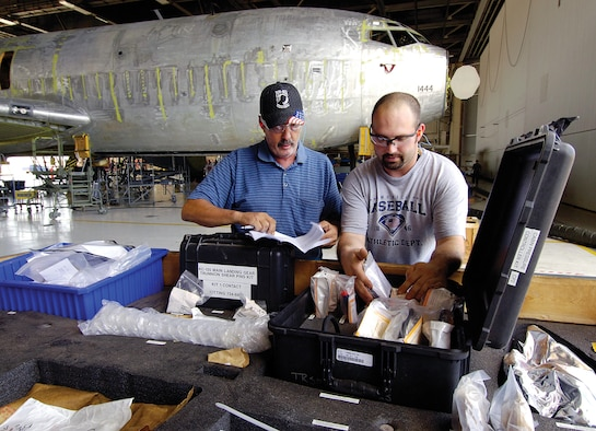 """Tinker aircraft work leader Russell Parris, left, and material expeditor Wesley Hugert look througha KC-135 super kit in the 564th Air Craft Maintenance Squadron Inspection Dock located in Bldg. 3102. The kit was a time-saving solution that slashes days from production and improves mechanics' work flow by having parts ready and waiting for the aircraft's arrival. Three such kits are used in the docks with another, always ready to go, said Mr. Hubert who helps build them. """"Before, we had to wait for a part and hope what you needed came in because we couldn't order parts early,"""" said Mr. Paris. """"Now the kits are built and waiting on the aircraft from day one,"""" KC-135 Program Depot Maintenance Production improvements like this helped the Oklahoma City Air Logistics Center earn the 2011 Robert T. Mason Depot Maintenance Excellence Award. (Air Force Photo by Margo Wright)"""