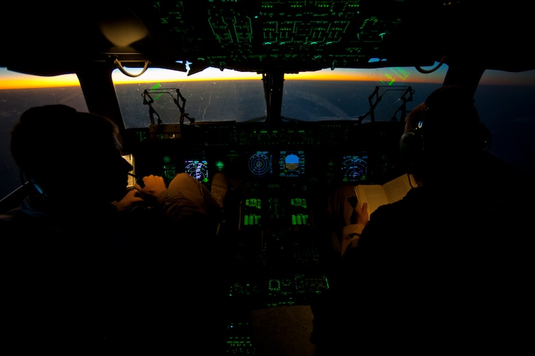 Capts. Matt Hammerle, left, and Eric Bowers, 817th Expeditionary Airlift Squadron pilots, reference flight material onboard a C-17 Globemaster III aircraft Aug. 18, 2011, while flying over Afghanistan. The crew transported equipment and supplies from Incirlik Air Base, Turkey, to Kandahar Air Field, Afghanistan. (U.S. Air Force photo by Tech. Sgt. Michael B. Keller/Released)