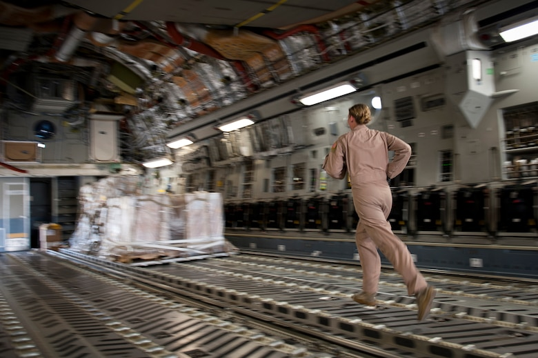 Staff Sgt. Melissa Butterfield, an 817th Expeditionary Airlift Squadron loadmaster, hurries to a pallet of cargo while unloading a C-17 Globemaster III aircraft Aug. 18, 2011, at Kandahar Air Field, Afghanistan, during a mission to transport equipment and supplies from Incirlik Air Base, Turkey. Loadmasters not only ensure the cargo is properly secured during flight, but also help with the unloading. (U.S. Air Force photo by Tech. Sgt. Michael B. Keller/Released)