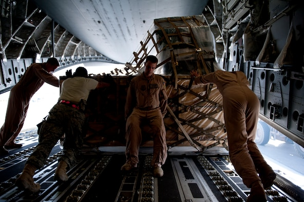 An 817th Expeditionary Airlift Squadron aircrew and 451st Expeditionary Logistics Readiness Squadron aerial port flight members unload a C-17 Globemaster III aircraft Aug. 18, 2011, at Kandahar Air Field, Afghanistan. The 817th EAS crew transported equipment and supplies from Incirlik Air Base, Turkey. (U.S. Air Force photo by Tech. Sgt. Michael B. Keller/Released)