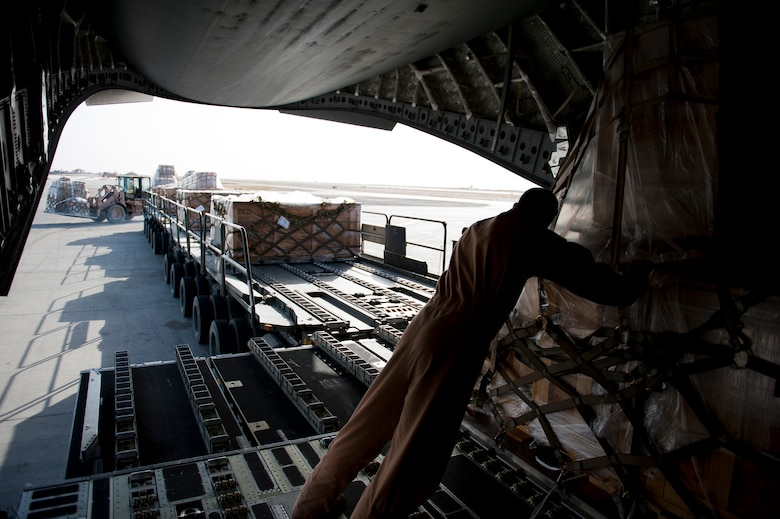 Staff Sgt. Sean Sullivan, an 817th Expeditionary Airlift Squadron loadmaster, pushes cargo while unloading a C-17 Globemaster III aircraft Aug. 18, 2011, at Kandahar Air Field, Afghanistan, during a mission to transport equipment and supplies from Incirlik Air Base, Turkey. Loadmasters not only ensure the cargo is properly secured during flight, but also help with the unloading. (U.S. Air Force photo by Tech. Sgt. Michael B. Keller/Released)