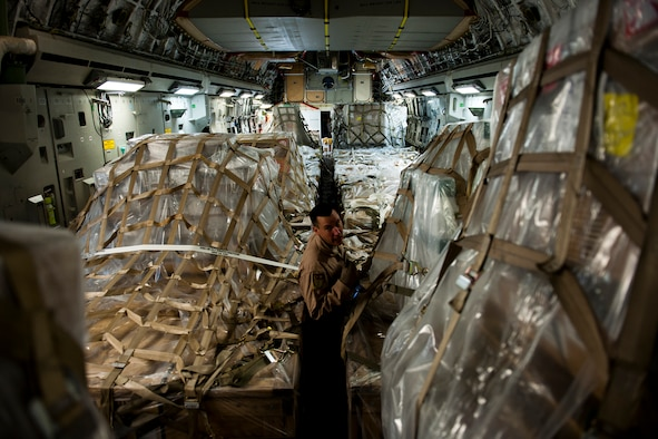Staff Sgt. Sean Sullivan, an 817th Expeditionary Airlift Squadron loadmaster, inspects cargo onboard a C-17 Globemaster III aircraft Aug. 18, 2011, at Incirlik Air Base, Turkey, prior to a mission to transport equipment and supplies to Kandahar Air Field, Afghanistan. Loadmasters ensure the cargo is properly secured to prevent movement during flight. (U.S. Air Force photo by Tech. Sgt. Michael B. Keller/Released)