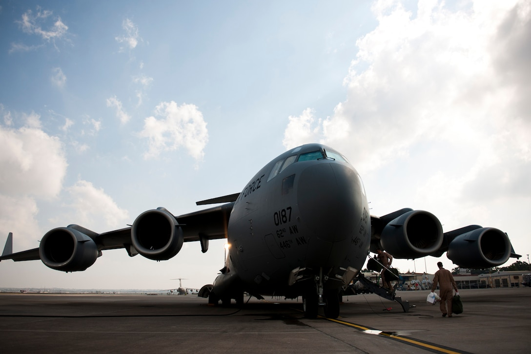 Capts. Matt Hammerle, left, and Eric Bowers, 817th Expeditionary Airlift Squadron pilots, load their flight equipment onto a C-17 Globemaster III aircraft Aug. 18, 2011, at Incirlik Air Base, Turkey. The crew transported equipment and supplies to Kandahar Air Field, Afghanistan. (U.S. Air Force photo by Tech. Sgt. Michael B. Keller/Released)
