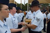 An airman receives an Airman's Coin from her military training instructor during graduation week.