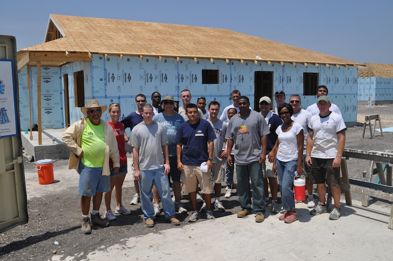 Eighteen of 25 volunteers from the 67th Network Warfare Wing pose for a group shot at the Habitat for Humanity-San Antonio build site Aug. 11. The team battled against sweltering heat and bees sharing the drinking water to build the first layer of the roof. More than 12,000 people volunteer at the site each year. (U.S. Air Force photo by Tech. Sgt Scott McNabb)
