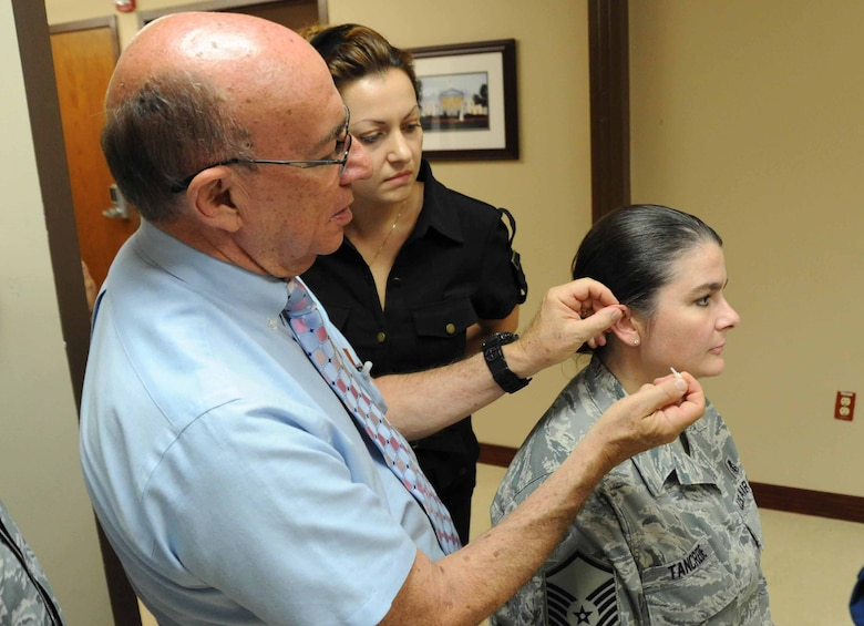 Retired Col. Richard Niemtzow, Air Force Acupuncture Clinic director, shows observing healthcare professionals how to properly apply the acupunture needle into Master Sgt. Michelle Tancrede's, 779th Aerospace Medical Squadron mission operations NCO in charge, ear during the battlefield acupuncture course here Aug. 12. Battlefiled acupuncture is a simple easy to use technique that offers fast and effective pain relief. (U.S Air Force photo/ Bahja J. Jones)