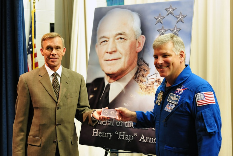 """DAYTON, Ohio -- Astronaut Gregory H. Johnson (right) presents Museum Director Lt. Gen. (Ret.) John L. """"Jack"""" Hudson (left) with a set of Gen. Hap Arnold's 5-star insignia, which was carried aboard the Space Shuttle Endeavour as it made its final voyage into space. During Family Day on Aug. 20, 2011, Johnson discussed his mission as pilot on Endeavour's last flight and returned the insignia to the museum. (U.S. Air Force photo by Jermont Chen)"""
