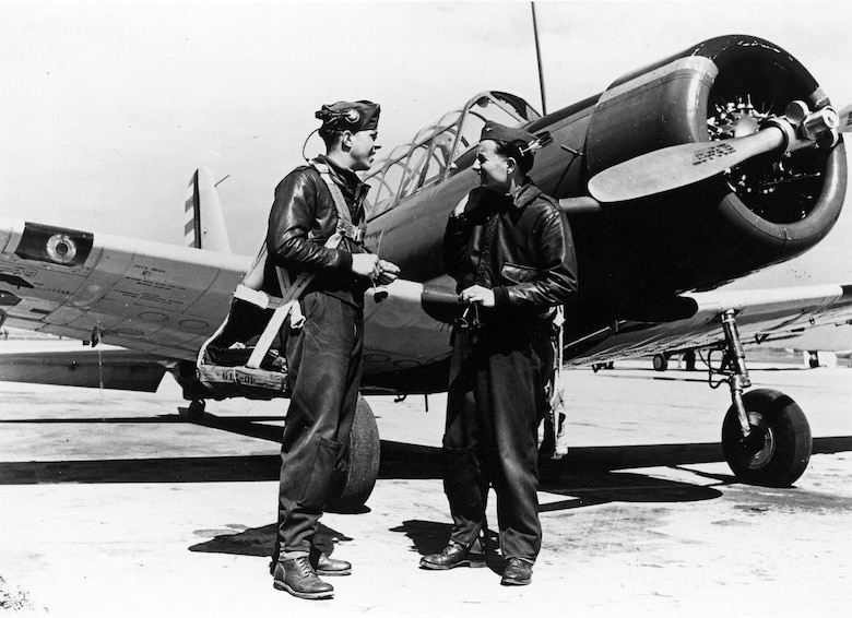 Flight students Jim Leach (left) and Jack Hoover beside a BT-13 basic trainer. Enlisted ground crew personnel formed a silent cheering section for enlisted pilot trainees and showed it in such ways as having a frosty soft drink ready for a sweat-stained student on a hot day. (U.S. Air Force photo)