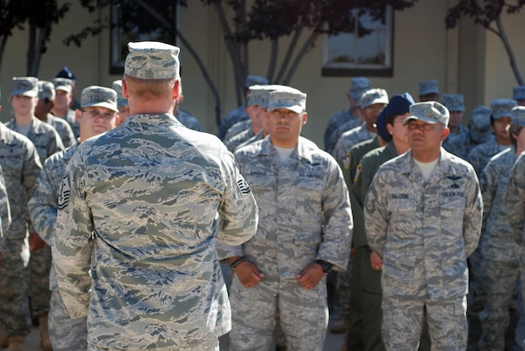 An Airman speaks to the members of a formation in front of the 452nd Air Mobility Wing headquarters building at March Air Reserve Base, Calif., Aug. 21, 2010. (U.S. Air Force photo by Staff Sgt. Kevin Chandler)