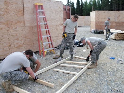 148th Fighter Wing Civil Engineering Squadron members Staff Sgt. Tom Jackson, Staff Sgt. Michael Wing, Senior Airman Brent Micken, and Airman 1st Class Jacob Olson construct part of asimulated village at Fort Greely, Delta Junction, Alaska July 23, 2011. The Army will use the village to train tactical movements and building clearing procedures.