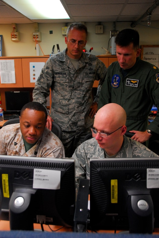 Master Sgt. Bohdan Pywowarczuk, Lt. Cdr. William Nink, (top) Sgt. Christopher Generette and SrA Sean Tinsley perform a quality check on an Air Tasking Order prior to publication, Aug. 24. during Ulchi Freedom Guardian 2011 exercise on Osan Air Base, Rupublic of Korea. (U.S. Air Force photo/Master Sgt. Kimberly Spinner)