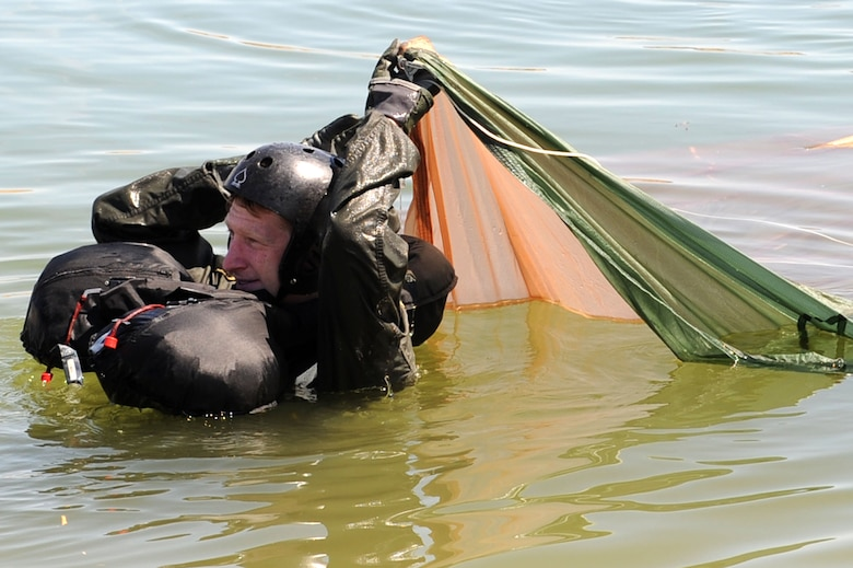 U.S. Air Force Capt. Justin Elliot, 422nd Test and Evaluation Squadron, F-15E Strike Division pilot, slides underneath a parachute during water survival training at Lake Mead, Nev. Aug. 17, 2011,  SERE specialists train high risk aircrew personnel to survive, evade, and return should they eject, bailout, or otherwise become isolated during combat, anywhere in the world. (U.S. Air Force photo by Staff Sgt. Taylor Worley/Released)