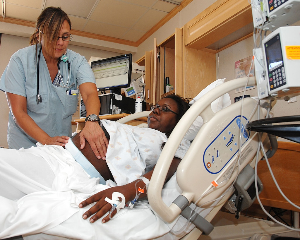 Angie Hudson (left) monitors Jennae Richards? contractions during her labor in the Hauth Birthing Center at Wilford Hall Medical Center July 8, 2011.  Hudson is a nurse assigned to the 59th Medical Inpatient Squadron. (U.S. Air Force Photo by Staff Sgt. Josie Walck)