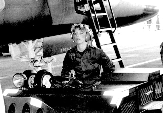 """Tech. Sgt. Pamela McNair-Foust operates a weapons loading vehicle known as a jammer at RAF Lakenheath England during the 1985 U.S. Air Forces in Europe """"Loadeo"""" competition. McNair-Foust armed four of the F-111 aircraft used in the U.S. military's 1986 Operation El Dorado Canyon. Today she assists international F-16 student pilots in training at the 162nd Fighter Wing at Tucson International Airport. (U.S. Air Force photo)"""
