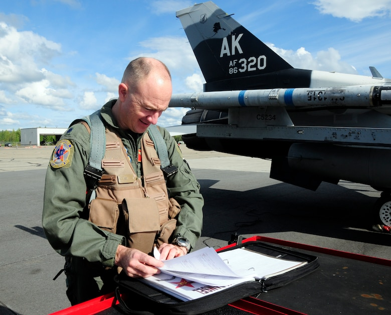 Aggressor pilot Lt. Col. Todd Emmons reviews aircraft maintenance forms before a flight here Monday. The aggressors act as the red forces, or bad guys, in training missions during RED FLAG-Alaska. Colonel Emmons is the 18th Aggressor Squadron commander. (U.S. Air Force photo/Senior Airman Rachelle Coleman)