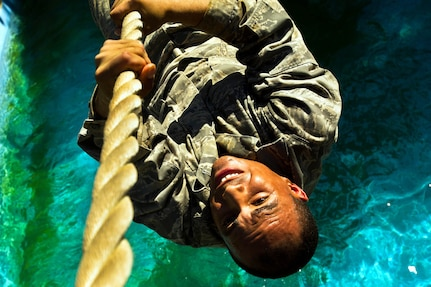 An Air Force basic military trainee attempts to finish an obstacle without falling off July 25 at Lackland Air Force Base. The obstacle course consists of 20 challenges designed to test strength, endurance and will power. (U.S. Air Force photo/Staff Sgt. Jonathan Snyder)