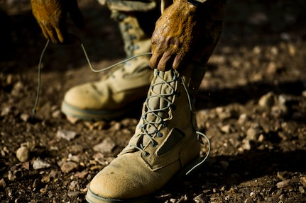 An Air Force basic military trainee reties his boots after completing the uphill low-crawl obstacle, part of the Creating Leaders, Airmen and Warriors (CLAW) course, July 27 at Lackland Air Force Base.  CLAW is a three-hour mission-oriented exercise designed to test teamwork, leadership skills and the ability to perform under pressure. (U.S. Air Force photo/Senior Airman Marleah Miller)