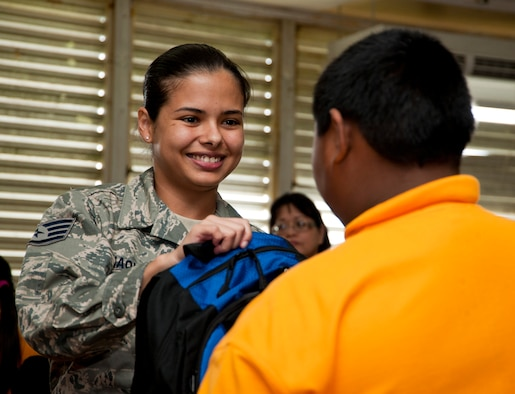 TALOFOFO, Guam— U.S. Staff Sgt. Sophia Idiaquez, 9th Operations Group Detachment 3 maintenance scheduling and planning, gives a backpack to a child from  the Talofofo Elementary School Aug. 25. The 9th OG adopted the Talofofo village and works closely with the local community throughout the year. (U.S. Air Force photo by Senior Airman Benjamin Wiseman/Released)