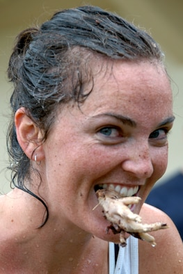 Nellie Boyer, a Team Andersen dependant, clenches a chicken's foot, and ultimately second place during Andersen's Annual Fear Factor challenge. More than 20 competitors participated in the challenge for a grand prize of two $200 Delta Airlines travel vouchers. In the end, Jacob Greathouse, a Team Andersen dependant, was able to clench victory and the grand prize for the second consecutive year. (U.S. Air Force photo by Senior Airman Carlin Leslie)