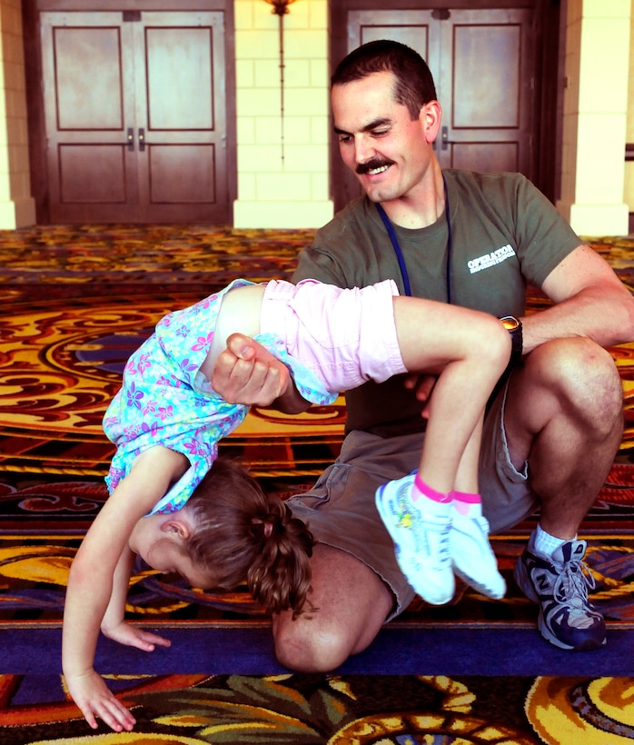 Navy Aircraft Structural Mechanic First Class Charles Peterman gives four-year-old daughter Alyssa a boost in her back handspring during a Yellow Ribbon Reintegration event at a Dallas-area hotel August 27. Peterman returned to NAS Fort Worth JRB, Texas, a few days ago from a year-long deployment to Afghanistan and attended the event with his wife Wendy and their children Aiden, Alyssa and Austin. The Yellow Ribbon Reintegration Program was initiated by Congress in 2008, and offers access to information, resources, and benefits to National Guard and Reserve servicemembers and their families before, during, and after deployments.  (U.S. Air Force photo/Senior Airman Martha Whipple)