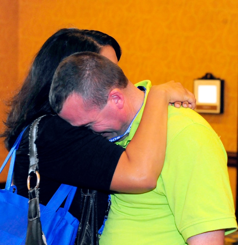 Tech. Sgt. Kelley Moore stands in the embrace of his wife, Erica. Moore, Air National Guardsman with the 147th Civil Engineer Squadron at Ellington Field, Texas, returned from a desert deployment in May. The couple attended the Yellow Ribbon Reintegration event at a Dallas-area hotel August 27. The Yellow Ribbon Reintegration Program was initiated by Congress in 2008, and offers access to information, resources, and benefits to National Guard and Reserve servicemembers and their families before, during, and after deployments.   (U.S. Air Force photo/Senior Airman Martha Whipple)