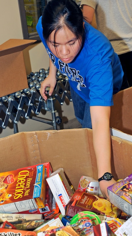 Cadet 2nd Class Jessica Wong gathers boxed goods to prepare a food package during the Air Force Academy Cadet Interfaith Council's volunteer effort at the Care and Share Food Bank of Southern Colorado Aug. 27, 2011. The Interfaith Council began the monthly volunteer project as part of its plan to participate in the White House's Interfaith and Community Service Campus Challenge. Wong, one of the cadets on the Interfaith Council, is assigned to Cadet Squadron 18. (U.S. Air Force photo/Sarah Chambers)