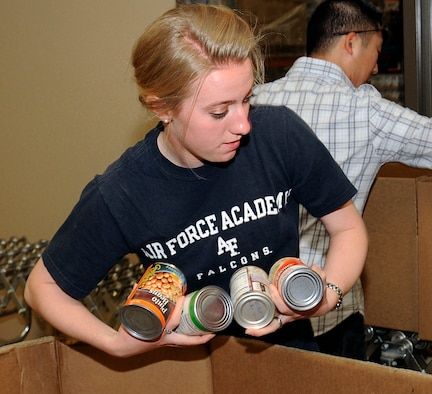 Cadet 3rd Class Tirzah Prince gathers canned goods to make a box of food at the Care and Share Food Bank of Southern Colorado Aug. 27, 2011. Care and Share was founded approximately 35 years ago and distributed approximately 18.5 million pounds of food throughout Southern Colorado in its 2010 fiscal year. Prince is assigned to Cadet Squadron 29. (U.S. Air Force photo/Sarah Chambers)