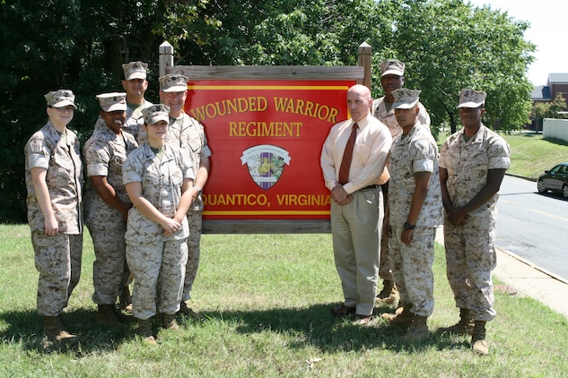 Mark Brokaw, program manager of the Wounded Warrior Regiment's Reserve Medical Entitlements Determination section, stands outside of the Regiment's headquarters aboard Marine Corps Base Quantico, Va., with the RMED section staff.  The RMED section tracks and manages the non-medical and medical care of wounded, ill and injured reserve Marines nationwide.