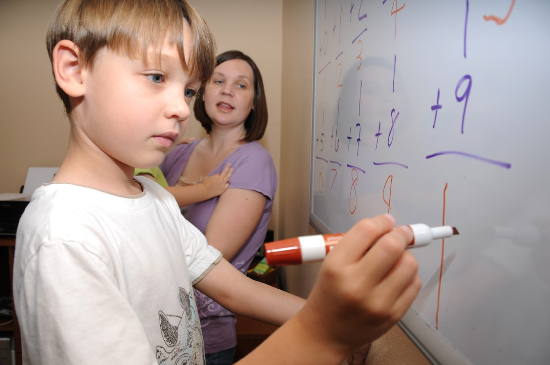 Jack Stratton, 6, reviews math problems with his mom, Teresa, at their home in Gulfport. Jack is a first grader this year.  Teresa is married to Maj. Matthew Stratton, 335th Training Squadron weather training flight commander.  (U.S. Air Force photo by Kemberly Groue)
