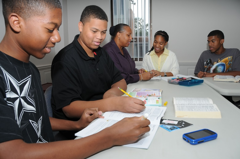The Elliotts, from left, are William, 15; Chris, 16; Mrs. Cherie Elliott; Sydney, 13; and Ralph, 17. With mom's help, William, Chris and Sydney review lessons prior to the start of the new school year while Ralph does some leisure reading. This home schooling session was held at the Triangle Annex because Mrs. Elliott had a gospel service leaders meeting there.  Cherie Elliott is married to Chaplain (Capt.) Ralph Elliott, who's currently deployed.  (U.S. Air Force photo by Kemberly Groue)